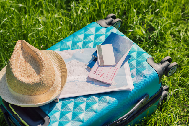passports, tickets, map, credit card and straw hat lying on blue suitcase