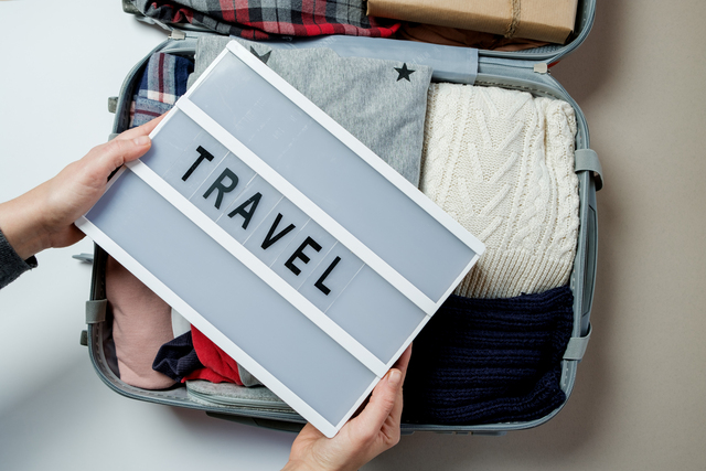 Woman hands with travel board on the background of Open suitcase